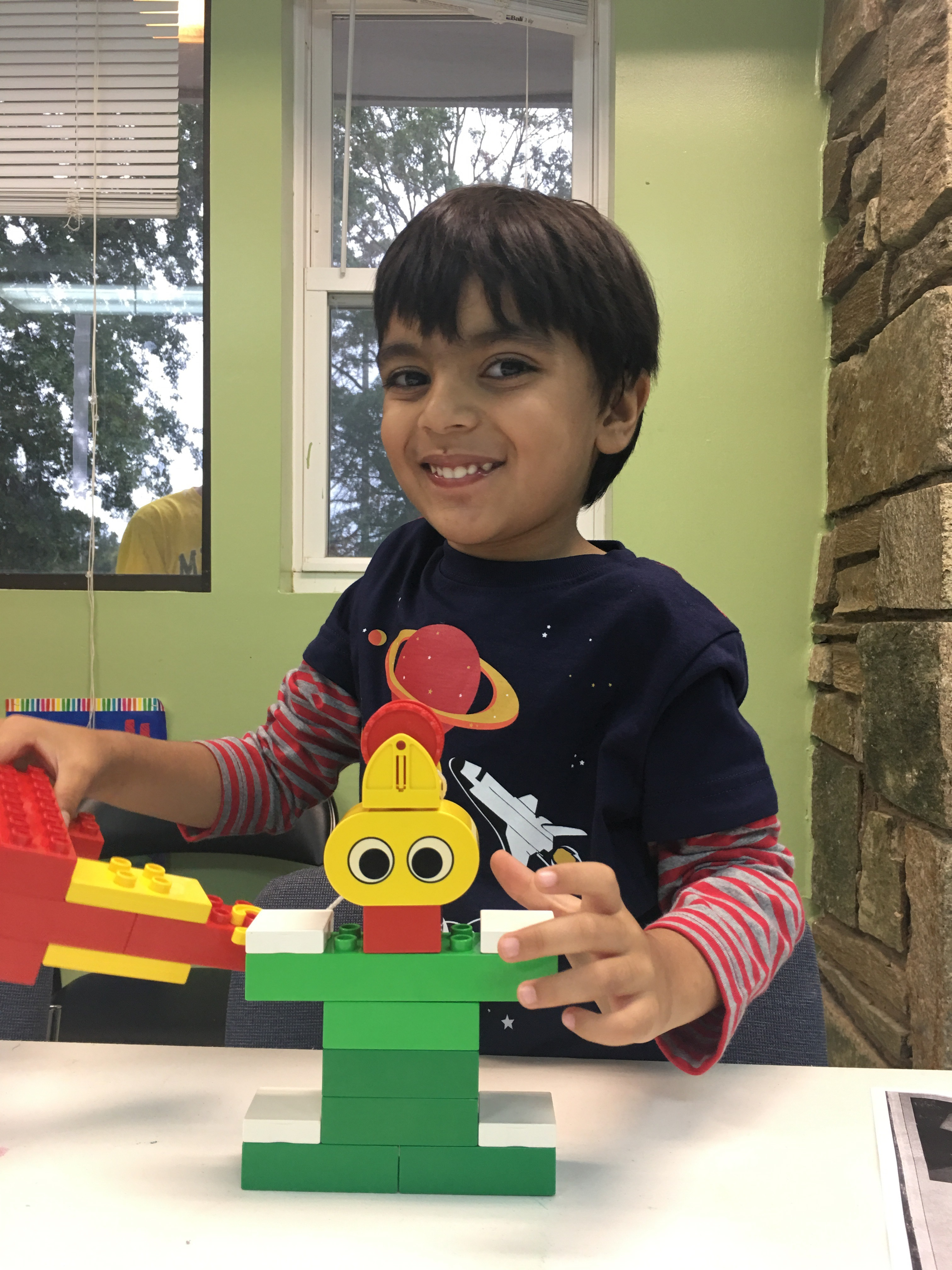 Happy 5 year old student working on his Early STEM project With